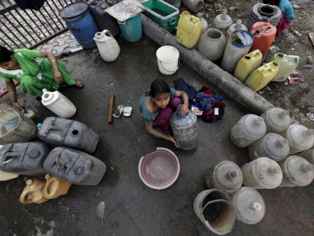 A girl waits to fill water in her containers from a municipal tap in New Delhi, India, February 21, 2016. PHOTO: REUTERS