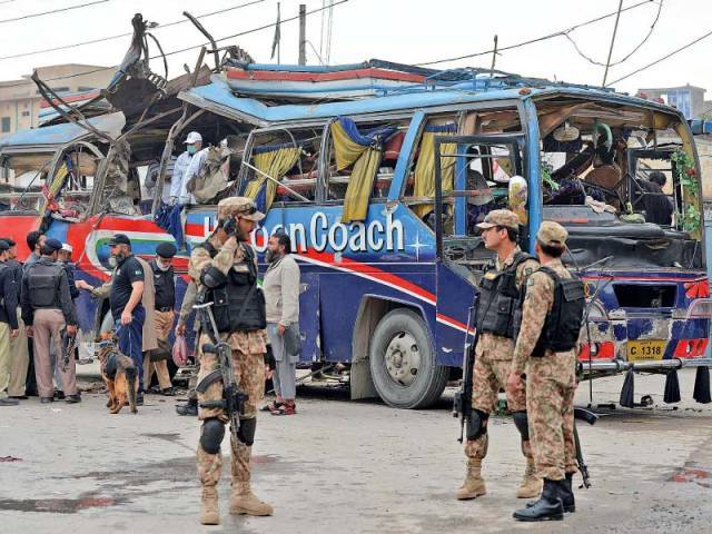 Security officials inspect the damaged bus after the blast. PHOTO: AFP
