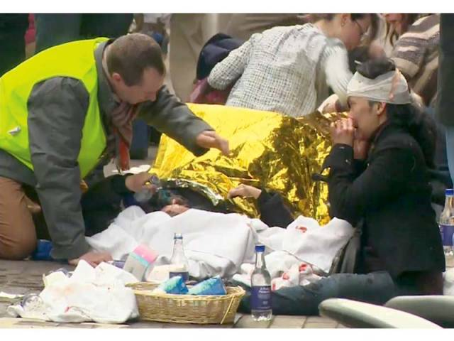 Rescuers treat victims outside the Maelbeek metro station in Brussels. PHOTO: REUTERS