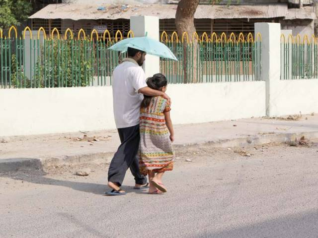 A man escorts a child to school carrying an umbrella to protect themselves from the heat. PHOTO: FILE
