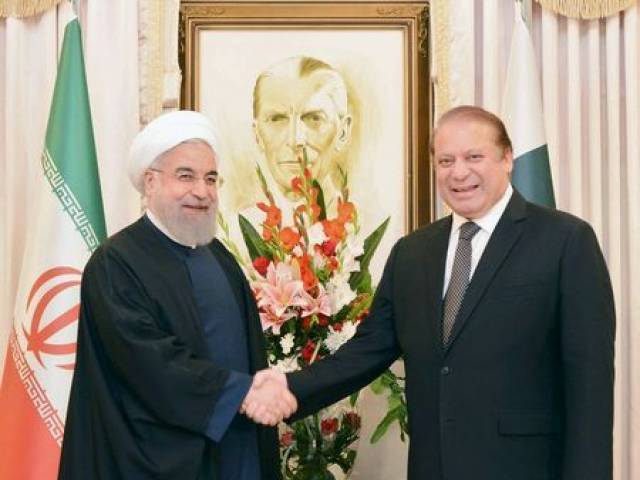 Prime Minister Nawaz Sharif shakes hands with Iranian President Hasan Rowhani. PHOTO: AFP