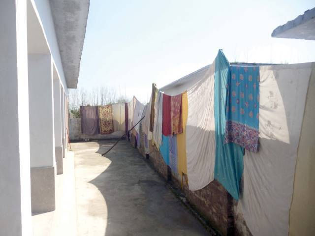 Students and teachers have  made a curtain from their own shawls to cover their school. PHOTO: EXPRESS