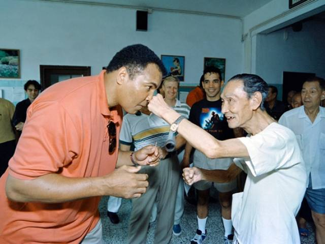 "(FILES) This file photo taken on September 01, 1994 shows Boxing great Muhammad Ali receiving a punch from a 79 old ""sparring-partner"" during a visit in a old people's home in Macau. Boxing legend Muhammad Ali, dies at 74. The former heavyweight world champion was hospitalized on Thursday at a Phoenix, Arizona, hospital with a respiratory issue, which US media reported was complicated by his Parkinson's disease. PHOTO: AFP"