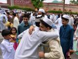 People exchange Eid greetings after offering Eidul Fitr prayers in Islamabad on July 29, 2014. PHOTO: AFP