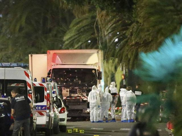 French police forces and forensic officers stand next to a truck July 15, 2016 that ran into a crowd celebrating the Bastille Day national holiday on the Promenade des Anglais killing at least 60 people in Nice, France, July 14. PHOTO: