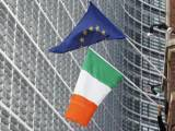 a-man-adjusts-an-irish-flag-as-it-flies-next-to-a-european-union-flag-near-the-eu-commission-headquarters-in-brussels
