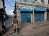 an-indian-policeman-stands-guard-in-front-of-closed-shops-painted-with-graffiti-during-a-curfew-in-srinagar