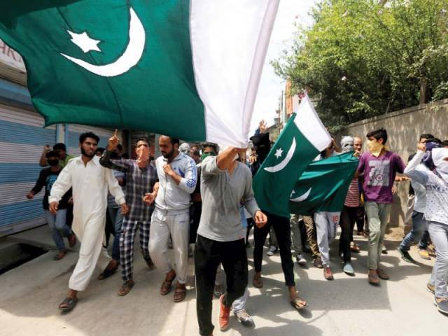 Pakistani flags hoisted and carried during a rally in Srinagar, Kashmir. PHOTO: REUTERS