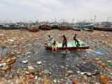 Boys aboard an abandoned boat collect recyclable items through polluted waters in front of fishing boats at Fish Harbor in Karachi, Pakistan, August 17, 2016. PHOTO: REUTERS