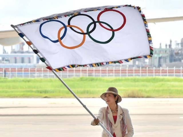Tokyo governor Yuriko Koike carried the flag during a ceremony at Haneda airport after stepping off a plane from the Brazilian host city, accompanied by a delegation who picked up a record 41 medals in Rio. PHOTO: AFP