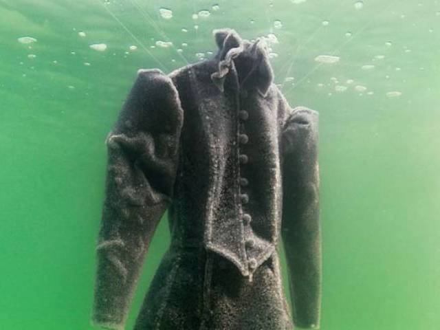 Artist submerges black dress in Dead Sea, salt turns it white