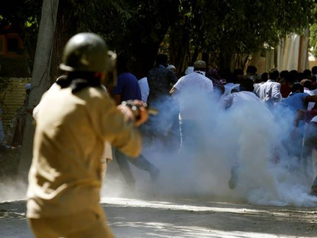 Protesters run away as a policeman fires tear gas towards them during a protest against the recent killings in Kashmir, on the outskirts of Srinagar, August 5, 2016. REUTERS/Danish Ismail