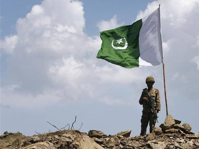 A soldier stands next to a Pakistani flag. PHOTO: REUTERS