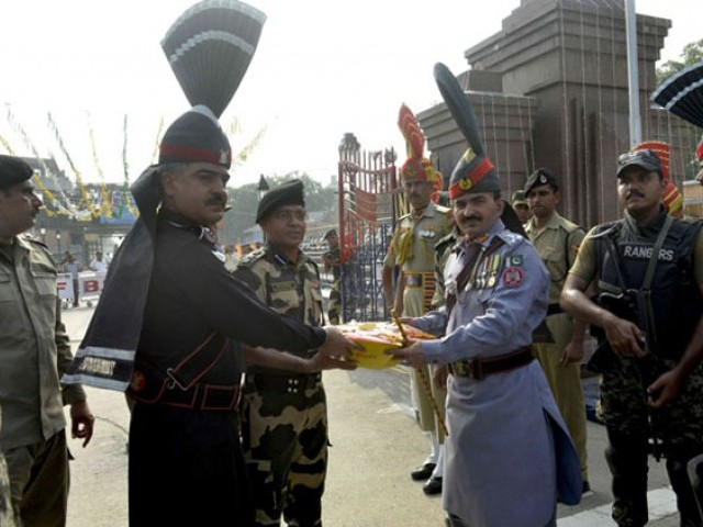 Pakistani Ranger Commander, Shaukat Ali (2R) presents sweets to Indian Border Security Force (BSF) Commandant Sudeep (3L) during a ceremony to celebrate Pakistan's Independence Day at the Pakistan-India Wagah border post on August 14, 2016 PHOTO: AFP