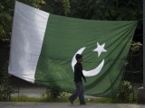 A boy walks past a Pakistani flag displayed for sale ahead of Pakistan's Independence Day, along a road in Rawalpindi. PHOTO: REUTERS