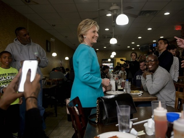 Democratic presidential nominee Hillary Clinton visits with customers at the Cedar Park Cafe November 6, 2016 in Philadelphia, PHOTO: AFP