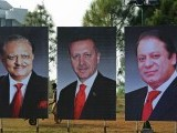 A Pakistani labourer works alongside portraits of Pakistan President Mamnoon Hussain (L) Pakistan Prime Minister Nawaz Sharif (R) and visiting Turkish Prime Minister Recep Tayyip Erdogan (C) on constitution avenue in Islamabad on December 22, 2013. Erdogan is scheduled to pay a two-day official visit to Pakistan from December 23, to discuss economic co-operation between the two countries.   AFP PHOTO/Farooq NAEEM