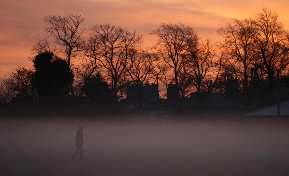 A woman walks through early morning mist in Knutsford, northern England December 5, 2016.  REUTERS/Phil Noble