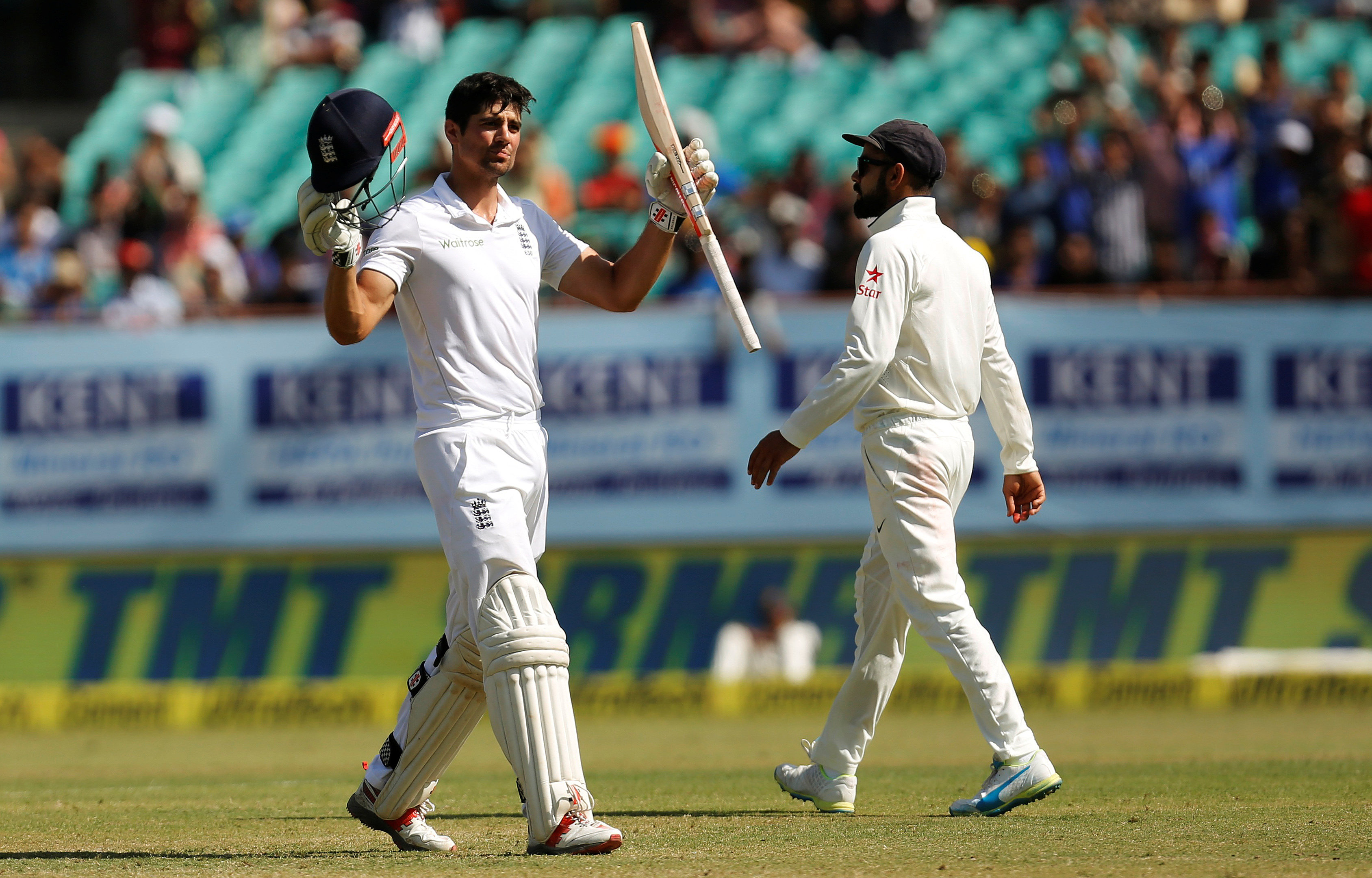 Alastair Cook celebrates his century as Virat Kohli (R) looks on. PHOTO: REUTERS/Amit Dave