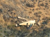 rescue-workers-survey-the-site-of-a-plane-crashed-a-day-earlier-near-the-village-of-saddha-batolni-near-abbotabad-pakistan