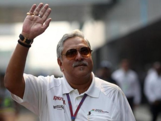 Force India team principal Vijay Mallya waves in the paddock  PHOTO: REUTERS