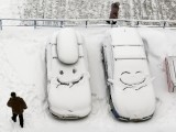 People walk past cars with faces which are scrawled on windscreens covered with snow after snowfall in Krasnoyarsk, Siberia, Russia, December 1, 2016. PHOTO: REUTERS