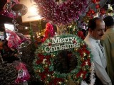 people-walk-past-an-artificial-decoration-wreath-hanging-outside-a-shop-selling-various-items-for-christmas-celebrations-in-karachi-2
