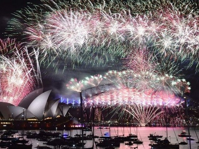 photo taken on January 1, 2016 shows fireworks lighting up the sky over Sydney's Opera House (L) and Harbour Bridge during New Year celebrations in Sydney. PHOTO: AFP