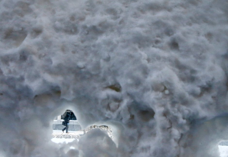 A person walks past a snow covered bus shelter during polar vortex in downtown Chicago, Illinois, U.S. on January 6, 2014.    REUTERS/Jim Young/File Photo