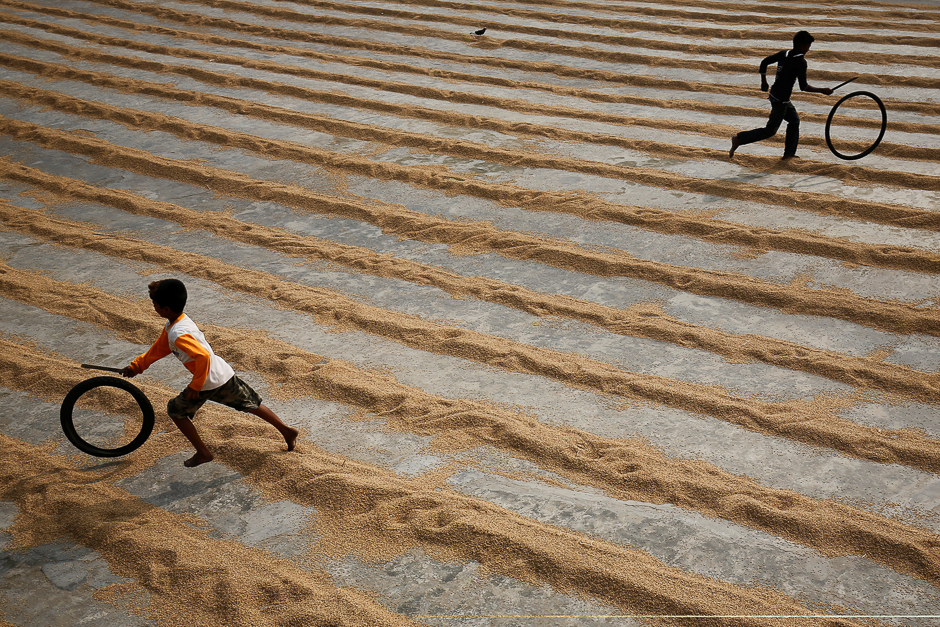 Children play with bicycle tires at a rice-processing mill in Muktarpur, on the outskirt of Dhaka, Bangladesh. PHOTO: REUTERS