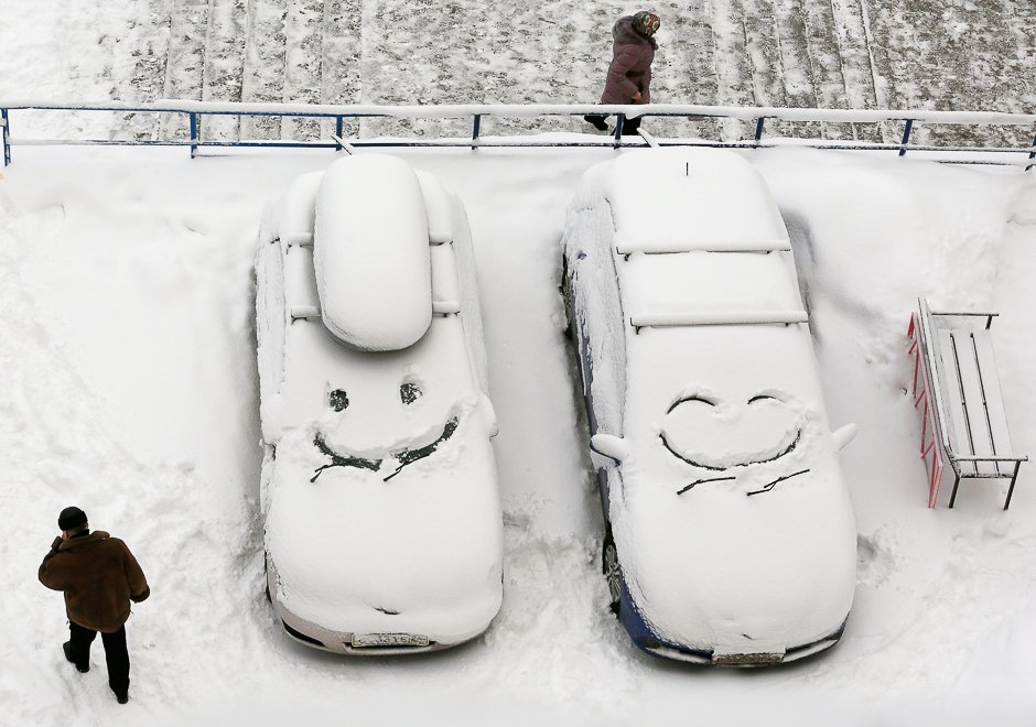 People walk past cars with faces which are scrawled on windscreens covered with snow after snowfall in Krasnoyarsk, Siberia, Russia, December 1, 2016. REUTERS/Ilya Naymushin