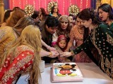 Guests cut a cake at Shakeela's party in Peshawar, Pakistan January 22,  2017. PHOTO: REUTERS