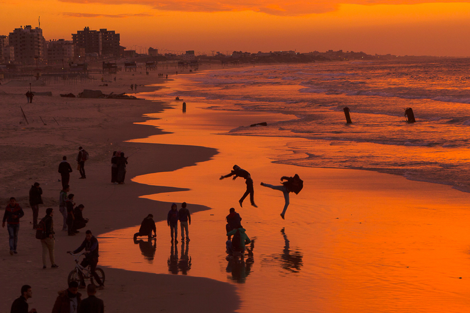 Palestinians make jumps on the beach during the sunset in Gaza City. PHOTO: AFP
