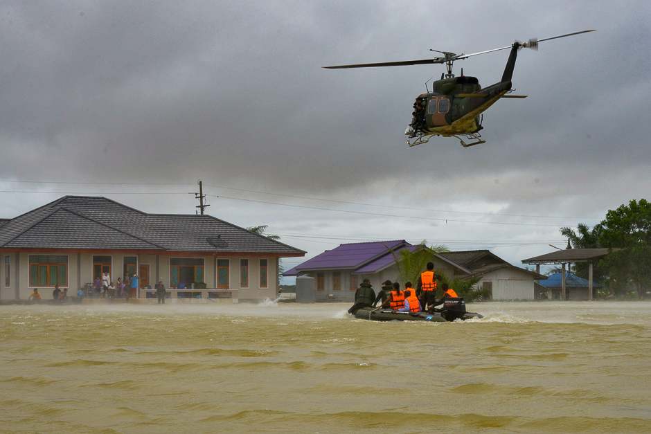 This photo shows a rescue boat and a helicopter moving towards a group of stranded people in the Srinakarin district of the southern Thai province of Phattalung. PHOTO: AFP