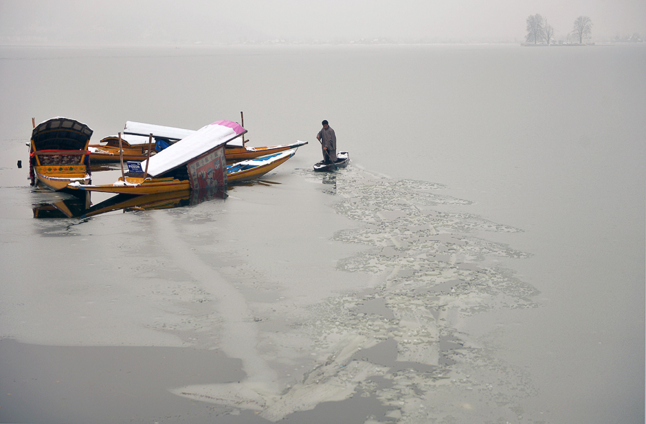 A Kashmiri boatman uses his oar to break the ice layer of the frozen Dal Lake after a heavy snowfall in Srinagar. PHOTO: AFP