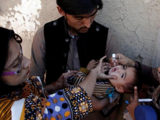 A boy receives polio vaccine drops by anti-polio vaccination workers along a street in Quetta, Pakistan January 2, 2017.  PHOTO: REUTERS