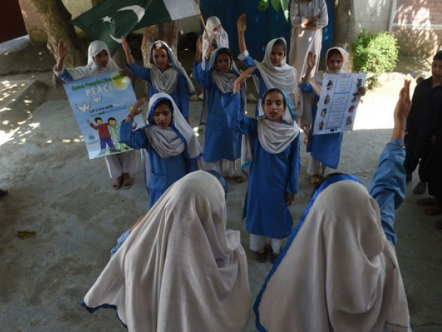 In this photograph taken on August 30, 2016, Hindko speaking schoolchildren sing the national anthem at their school in Mansehra.  Around a hundred women have gathered in a community centre in Peshawar, the heart of Pakistan's fabled northwest -- but they are conversing in a dialect incomprehensible to the Pashtun ethnic group that dominates the region. PHOTO: AFP