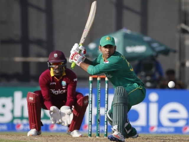 Pakistan T20I captain Sarfaz Ahmed (R) hits the ball as West Indies' wicketkeeper Densh Ramdin (L) fields. PHOTO: AFP