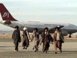 Armed Taliban fighters walk past the hijacked Indian Airlines plane at Kandahar airport. PHOTO: REUTERS