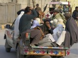 families-sit-in-the-back-of-a-vehicle-as-they-flee-a-military-offensive-and-enter-bannu