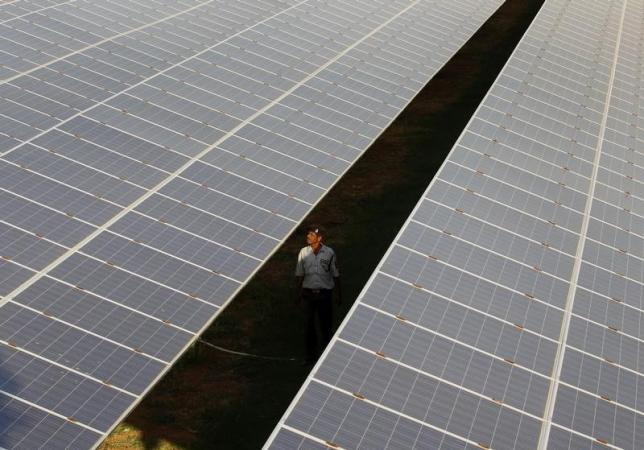 a-private-security-guard-walks-between-rows-of-photovoltaic-solar-panels-inside-a-solar-power-plant-at-raisan-3-2