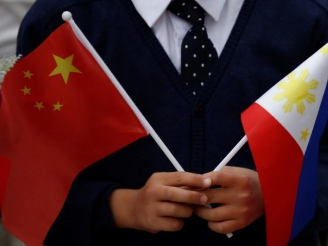 A child holds national flags of China and the Philippines before President of the Philippines Rodrigo Duterte and China's President Xi Jinping attend a welcoming ceremony at the Great Hall of the People in Beijing, China, October 20, 2016. PHOTO: REUTERS