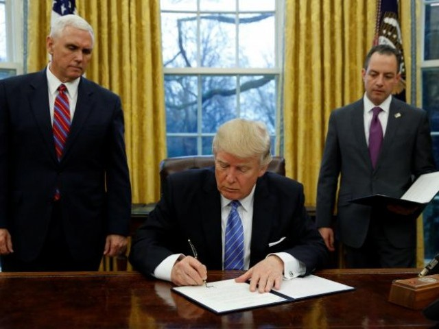 US President Donald Trump signs an executive order on US withdrawal from the Trans Pacific Partnership while flanked by Vice President Mike Pence (L) and White House Chief of Staff Reince Priebus (R) in the Oval Office of the White House in Washington January 23, 2017.  PHOTO: REUTERS