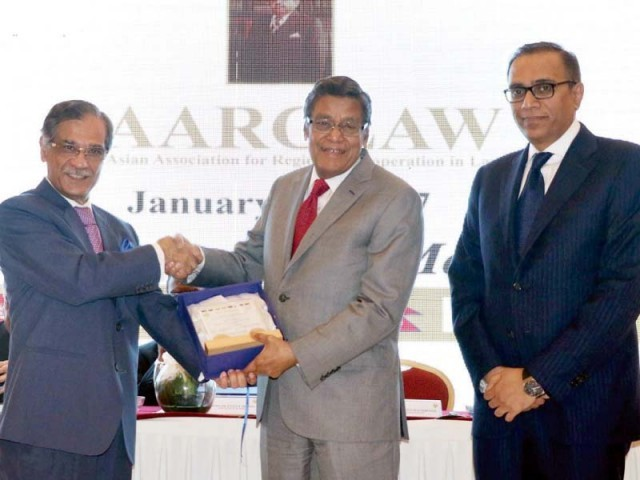 Chief Justice Saqib Nisar gives away a shield to Indian Supreme Court Advocate K K Venugopal in Karachi. PHOTO: ONLINE