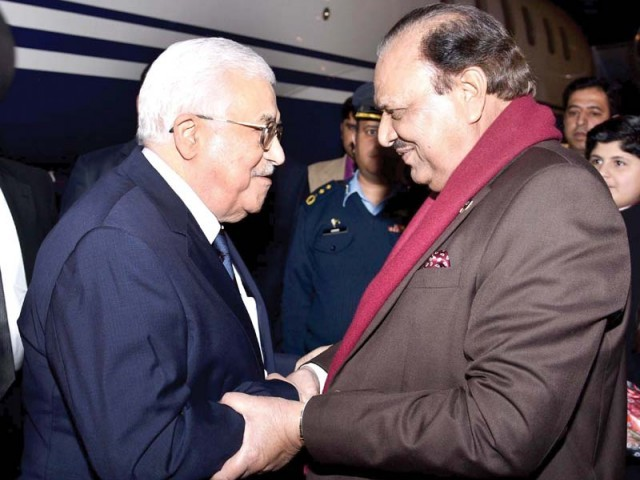 President Mamnoon Hussain greeting Palestinian President Mahmoud Abbas upon his arrival at the military airbase in Islamabad. PHOTO: AFP