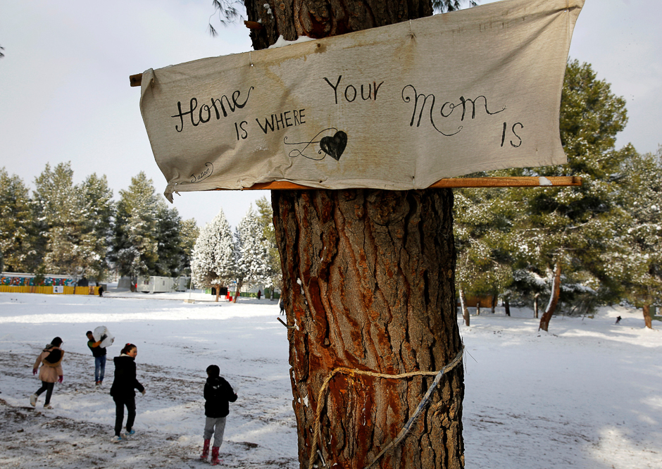 "A banner that reads, ""Home is where your mom is"" is attached to a tree at a refugee camp north of Athens as stranded Syrian refugee children play with snow. PHOTO: REUTERS"