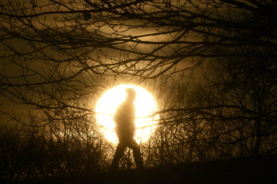 A walker is silhouetted in front of the setting sun on Primrose Hill in London, Britain. PHOTO: REUTERS