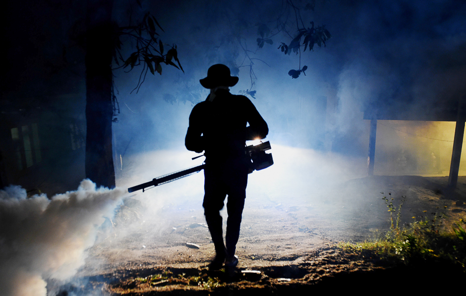 A Sri Lankan health worker sprays a neighbourhood with a fog used to ward off mosquitos in Biyagama on the outskirts of Colombo. PHOTO: AFP