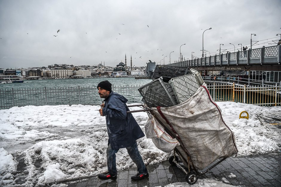 A trash collector walks next to the Galata bridge in Karakoy district after a snowfall in Istanbul on January. PHOTO: AFP