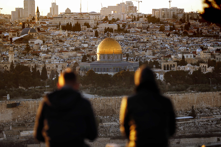 Two persons watch the sun setting on the Old City of Jerusalem, with the Muslim mosque of the Dome of the Rock in the center. PHOTO: AFP